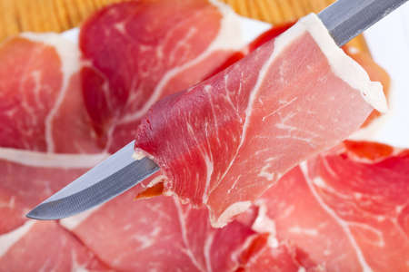 cut slices of ham with a carving knife on the plate out of focus