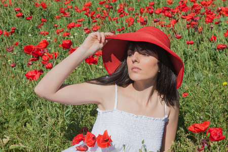 Niña Entre amapolas, sombrero rojo