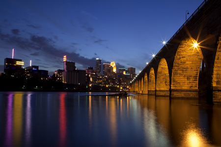 The famous Stone Arch Bridge at dusk with reflections in the Mississippi river in Minneapolis, Minnesota