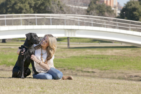 Young woman sitting and embracing her dog black labrador in Trinity Park in Ft Worth, Texas. Composition showing that dog and human being are two best friends. Copy Space