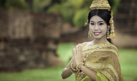 woman performing typical thai dance with thai style temple background, identity culture of thailand