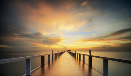 Wooded bridge in the port along sunrise.