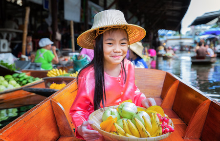 Photo pour Chikd sit on the boat and hold the fruit basket in Traditional floating market , Thailand. - image libre de droit
