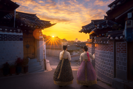 Photo for Asian lady in Hanbok dress walk togather in Korea old city with morning sunrise. - Royalty Free Image