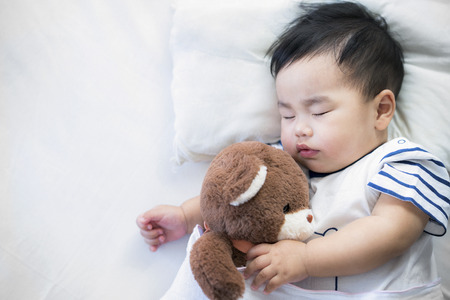 Foto de Newborn baby sleep with teddy bear on ther bed - Imagen libre de derechos