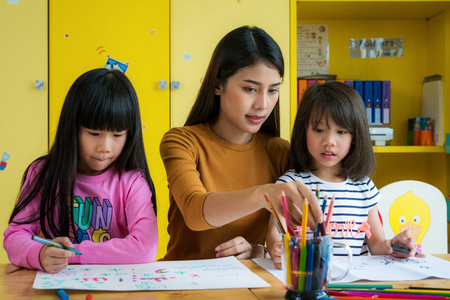 Photo pour Asian teacher and preschool student in art class, this immage can use for teacher, education, school, student, kid,art, and back to school concept - image libre de droit