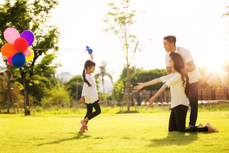 Foto de Asian family run and play in a garden, this immage can use for father, mother, kid and summer concept - Imagen libre de derechos