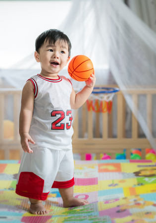 Photo pour Baby with ball in basketball uniform, this immage can use for play, sport, baby, child, kid and exercise work - image libre de droit