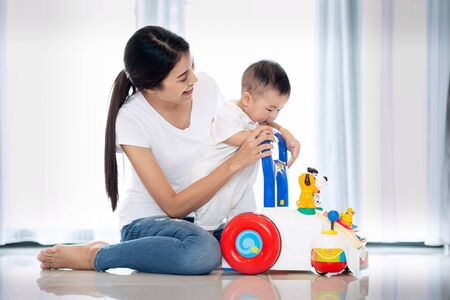 Photo pour Asian mother training walking to her baby by walking toy - image libre de droit