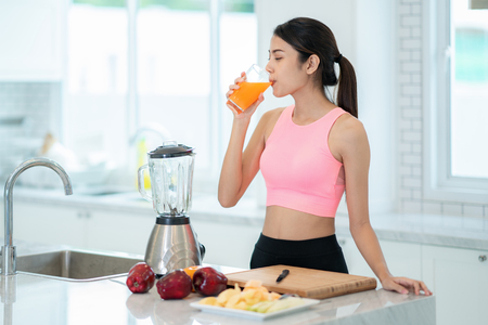 Photo pour Asian lady drink a mixed fruit for healthy in a kitvhen room - image libre de droit