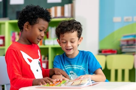 Photo pour Student in international preschool reading a magazine book together in school library, education, kid and study concept - image libre de droit