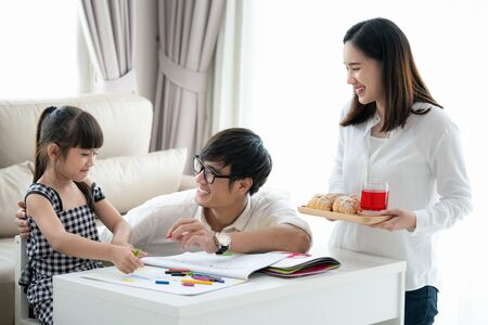 Foto de Asian family do homework together in living room, this picture can use for education, student, father, mother and home concept - Imagen libre de derechos