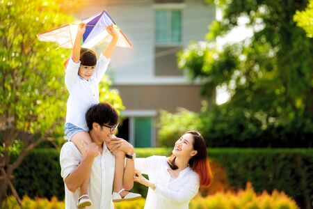 Foto de Asian family father, mother and daughter play a kite in the outdoor park in village near thay home, this image can use for family, relax, freedon, summer and travel concept - Imagen libre de derechos