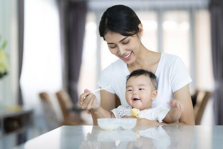 Foto de Asian mother feed soup to her baby, this image can use for baby, boy, mom and family concept - Imagen libre de derechos