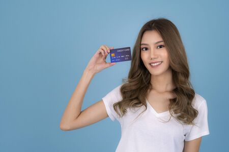 Photo pour Portrait of a lovely asian young girl in white T Shirt showing credit card and looking away at copy space isolated over blue background - image libre de droit