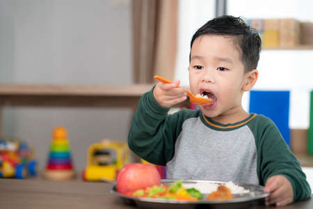 Photo pour Asian student take a lunch in class room by food tray prepared by his preschool, this image can use for food, school, kid and education concept - image libre de droit