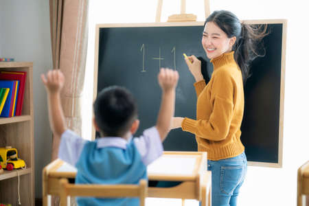 Photo pour Asian woman teacher and her smart student in class room with backboard background, this image can use for preschool, genius, clever, study, education and school concept. - image libre de droit