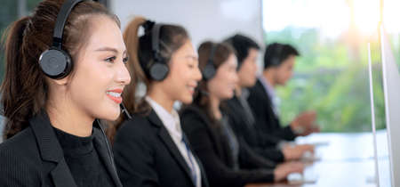 Photo pour Positive Asian Female Customer Services Agent With Headset Working In A Call Center company - image libre de droit