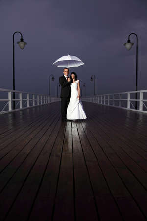 bride and groom, pier cloudy dusk sky.