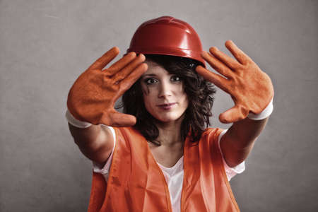 Sex equality and feminism. Sexy girl construction worker builder in orange vest and hard hat showing stop sign hand gesture.