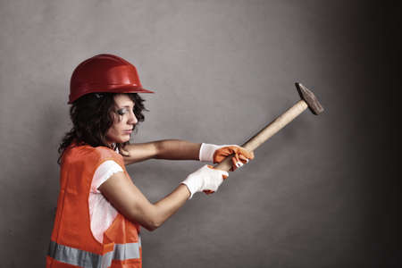 Sex equality and feminism. Sexy girl in safety helmet orange vest holding hammer tool. Attractive woman working as construction worker.