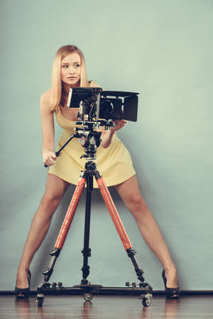 Photographer girl shooting images. Attractive fashionable blonde woman in full length taking photos with camera on blueの写真素材