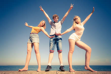 Friendship happiness summer holidays concept. Group of friends boy two girls having fun outdoor stretching arms celebrating, wide angle view
