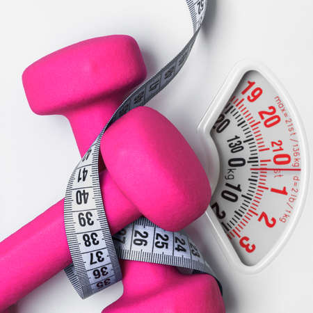 Photo pour healthy lifestyle fitness weight control concept. Closeup pink dumbbells with measuring tape on white scales - image libre de droit