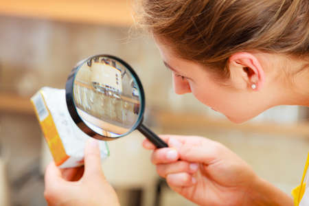 Photo pour Mature woman female inspecting testing butter food label with magnifying glass. - image libre de droit