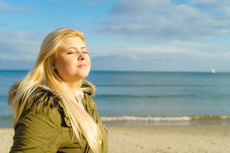 Photo pour Leisure, spending free time outside, healthy walks concept. Woman wearing warm jacket relaxing on beach near sea, cold sunny day - image libre de droit