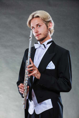 Classical music, passion and hobby concept. Portrait of elegantly dressed musician blonde young man holding flute. Studio shot on dark grey background