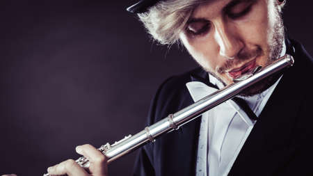 Classical music, passion and hobby concept. Elegantly dressed musician man playing on flute. Studio shot on dark grey background