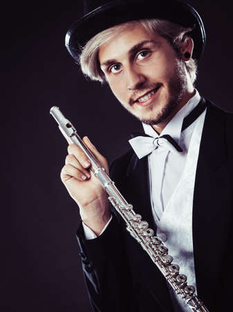 Classical music, passion and hobby concept. Elegantly dressed musician man holding flute wearing black hat. Studio shot on dark background