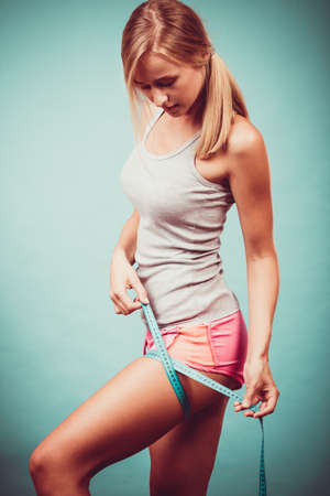Time for diet slimming weight loss. Fitness woman fit girl in sportswear with measure tape measuring her thigh on blue