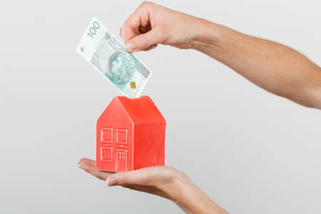 Household savings and finances, economy concept. Man putting zlotych money into a piggy bank in the shape of a house, studio shot on grey background