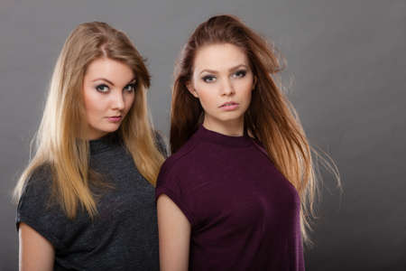 Family relationships, friendship concept. Two beautiful women sisters, blonde and brunette with windblown hair posing charmingly. Studio shot on dark grey background