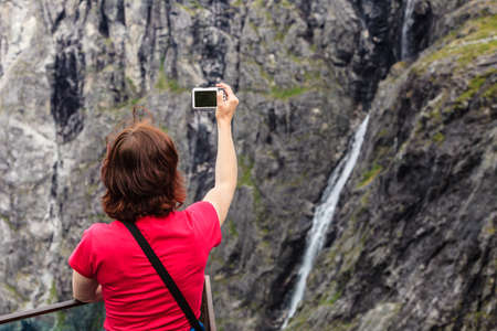 Travel, beauty in nature. Tourist woman looking at mountains, taking picture with camera from Trollstigen viewing point, Norway