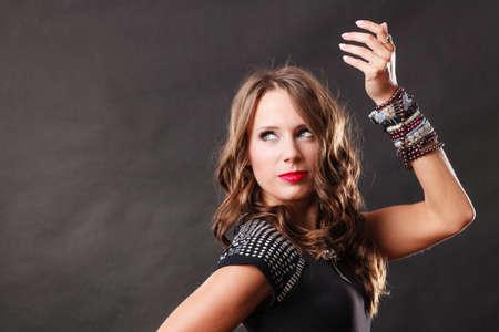 Photo pour Pretty young woman wearing multiple bracelets jewellery necklace in black elegant evening dress on dark - image libre de droit