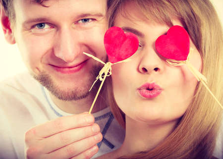 Love and happiness concept. Cheerful enjoyable young couple with little small hearts on sticks covering woman man eyes. Lovers blinded by their big love.の写真素材