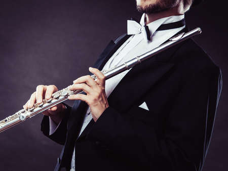 Classical music, passion and hobby concept. Elegantly dressed musician man holding flute. Studio shot on dark background