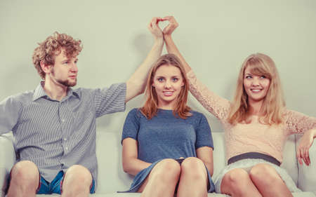Photo pour Happy young people sitting on sofa. Man and woman hiding their love. Cheating boyfriend with her girlfriend. - image libre de droit