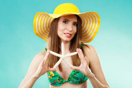 Summer holidays concept. Closeup woman in yellow hat bikini holding white shell starfish in hand on vivid blue background
