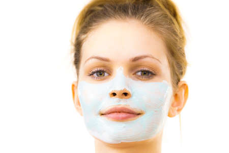 Photo pour Young woman applying green mud mask to face, on white. Teen girl taking care of oily skin, purifying the pores. Beauty treatment. Skincare. - image libre de droit