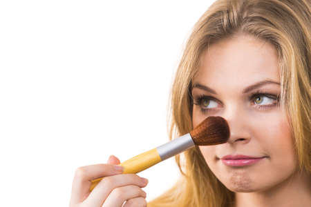 Photo pour Fashionable cheerful young female holding professional powder brush, adding last touch to her make up - image libre de droit