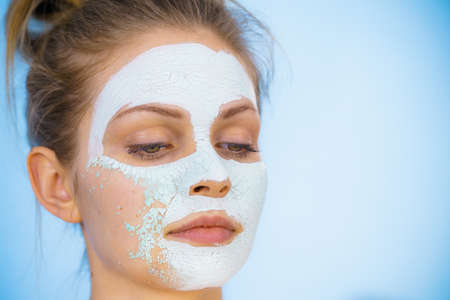 Photo pour Young woman with white dried mud mask on face being removing cosmetic. Teen girl taking care of oily skin. Beauty treatment. Skincare. - image libre de droit