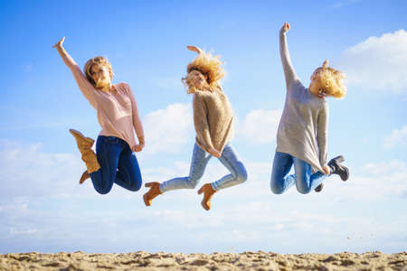 Photo pour Three women full of joy jumping around with sky in background. Female friends having fun outdoor. - image libre de droit