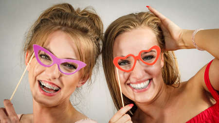 Photo pour Two happy women holding symbols on stick having fun pretending to wear eyeglasses. Photo and carnival funny accessories concept. - image libre de droit