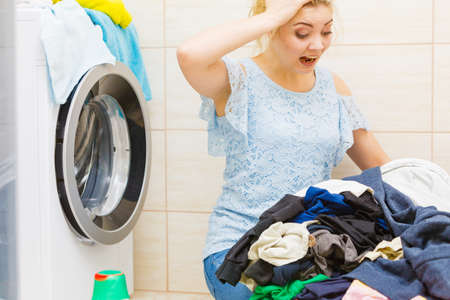 Photo pour Unhappy woman in bathroom with pile of dirty clothes laundry and damaged washing machine. Hard work, household duty. - image libre de droit