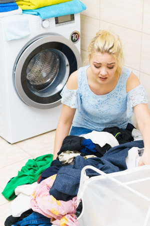 Photo pour Sad woman having a lot of laundry to make. Unhappy female surrounded by big clothing piles stack sitting next to washing machine being tired houseworking. - image libre de droit