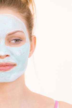 Photo pour Young woman with green mud mask on face, on white. Teen girl taking care of oily skin, purifying the pores. Beauty treatment. Skincare. - image libre de droit
